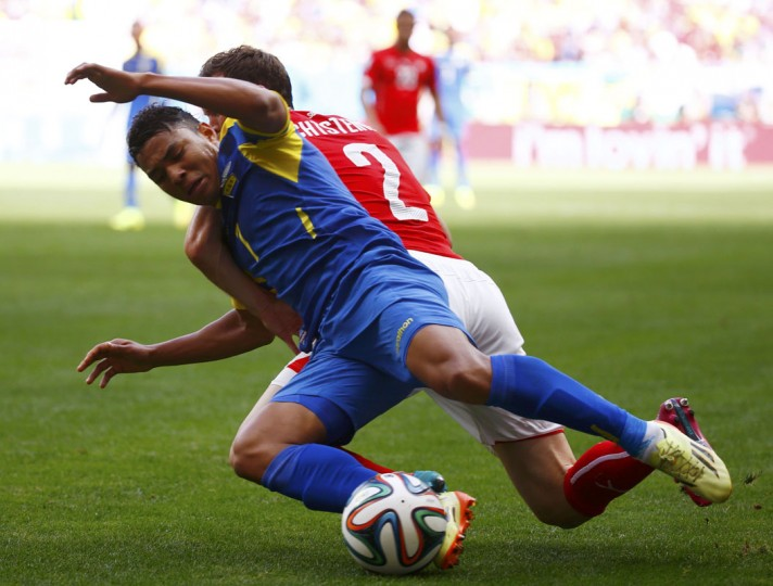 Ecuador's Jefferson Montero (L) fights for the ball with Switzerland's Stephan Lichtsteiner during their 2014 World Cup Group E soccer match at the Brasilia national stadium in Brasilia, June 15, 2014. (Paul Hanna/Reuters)