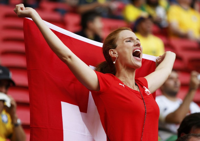 A Switzerland fan holding the national flag cheers before their 2014 World Cup Group E soccer match against Ecuador at the Brasilia national stadium in Brasilia, June 15, 2014. (Paul Hanna/Reuters)