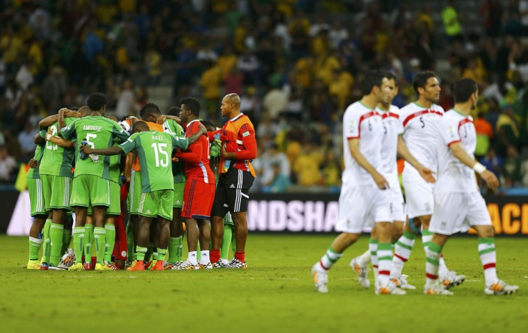 Nigeria players huddle, as Iran players walk past, at the end of their 2014 World Cup Group F soccer match at the Baixada arena in Curitiba on June 16, 2014. (REUTERS/Ivan Alvarado)