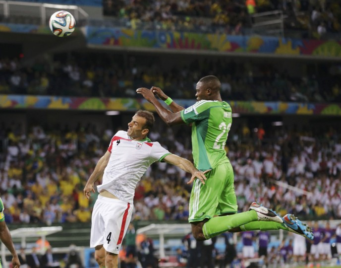 Iran's Jalal Hosseini (left) fights for the ball with Nigeria's Shola Ameobi during their 2014 World Cup F soccer match at the Baixada arena in Curitiba on June 16, 2014. (REUTERS/Henry Romero)