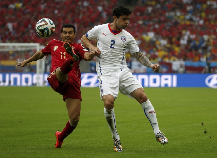 Spain's Pedro Rodriguez fights for the ball against Chile's Eugenio Mena (R) during their 2014 World Cup Group B soccer match at the Maracana stadium in Rio de Janeiro June 18, 2014. (Jorge Silva/Reuters)