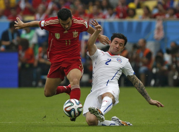 Spain's Pedro Rodriguez (L) and Chile's Eugenio Mena fight for the ball during their 2014 World Cup Group B soccer match at the Maracana stadium in Rio de Janeiro June 18, 2014. (Jorge Silva/Reuters)