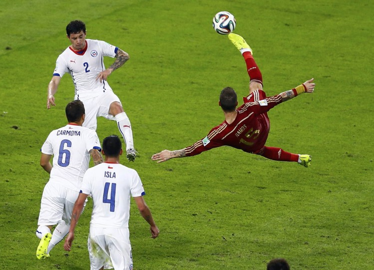 Spain's Sergio Ramos kicks the ball, as Chile's Eugenio Mena (top), Carlos Carmona and Mauricio Isla watch, during the 2014 World Cup Group B soccer match at the Maracana stadium in Rio de Janeiro June 18, 2014. (Ricardo Moraes/Reuters photo)