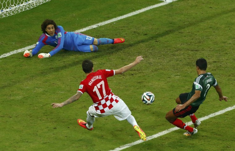 Mexico's Francisco Rodriguez (right) saves the ball in front of Croatia's Mario Mandzukic as Mexico's goalkeeper Guillermo Ochoa looks on during their 2014 World Cup Group A soccer match at the Pernambuco Arena in Recife June 23, 2014. (REUTERS/Ruben Sprich)