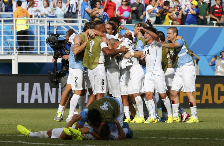 Uruguay's national soccer players celebrate at the end of the 2014 World Cup Group D soccer match against Italy at the Dunas arena in Natal on June 24, 2014. (REUTERS/Yves Herman)