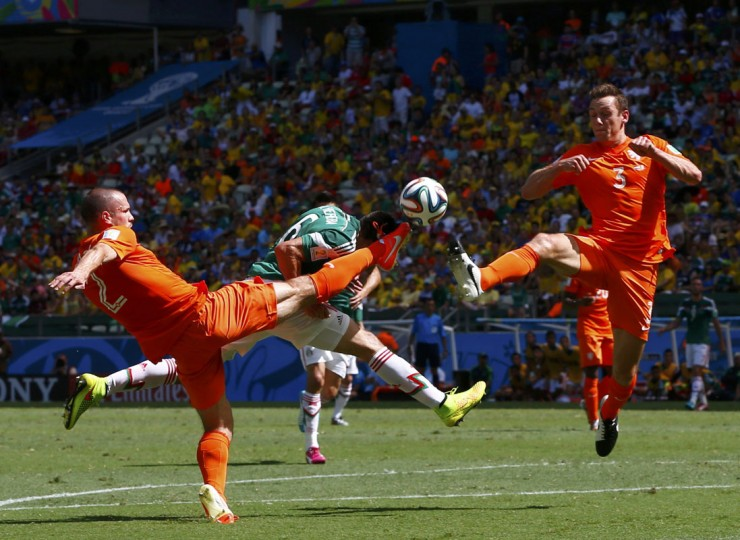 Mexico's Hector Herrera (C) fights for the ball against Ron Vlaar (L) and Stefan de Vrij of the Netherlands during their 2014 World Cup round of 16 game at the Castelao arena in Fortaleza June 29, 2014. (Eddie Keogh/Reuters)