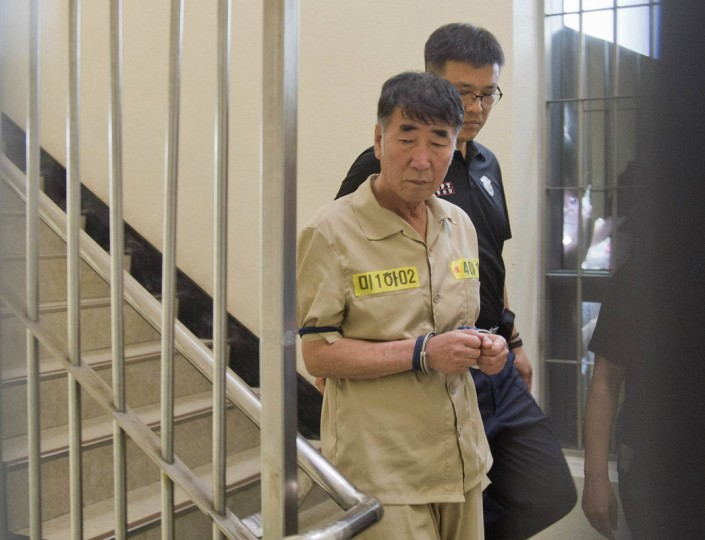 "Lee Joon-seok, captain of sunken ferry Sewol, arrives at a court in Gwangju June 10, 2014. Fifteen crew of a South Korean ferry that sank in April killing more than 300 people, mostly children, went on trial on Tuesday on charges ranging from negligence to homicide, with the shout going up of ""murderer"" as the captain entered the packed court. (Korea Pool/Yonhap/Reuters)"