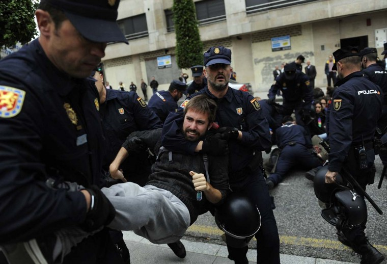 Spanish riot police remove activists of the group The Madrena during a rally in front of the occupied building in Oviedo, northern Spain June 3. A regional judge has ordered the eviction of The Madrena social centre after the owners of the buildings claimed their rights over the property.  || PHOTO CREDIT: ELOY ALONSO  - REUTERS