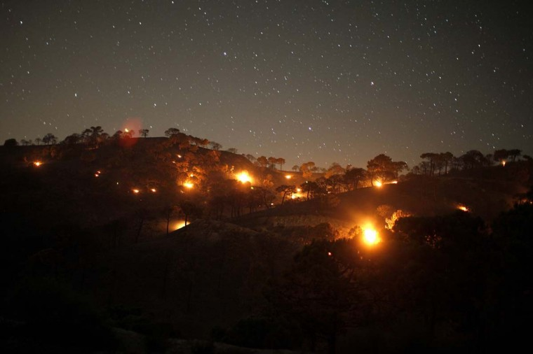 Small forest fires are pictured between pine trees at night at Sierra de Tejeda nature park, on a burnt mountain from El Collado mountain pass, near the town of Competa, near Malaga, southern Spain early June 30, 2014. A wildfire forced the evacuation of 600 people from their homes, most of the evacuated were resident tourists, as two houses were razed, according to local media. Picture taken using long exposure. (Jon Nazca/Reuters)