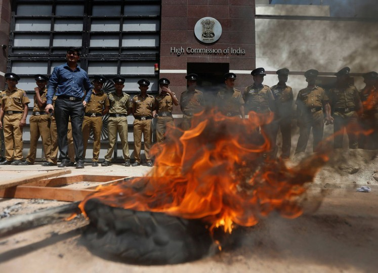 Police officers stand guard outside the Indian High Commission to Sri Lanka behind a tire set alight by demonstrators from the Freedom of National Organization, during a protest against Indian Prime Minister Narendra Modi, in Colombo June 10, 2014. Sri Lanka on June 4, 2014, again rejected devolving police powers to the provinces as requested by Modi and required by the constitution as a means to ease tension with minority Tamils. Sri Lanka agreed with India in 1987 to devolve powers, including over police and land, to a regional level as a means to improve relations between Tamils and majority Sinhalese. (Dinuka Liyanawatte/Reuters)
