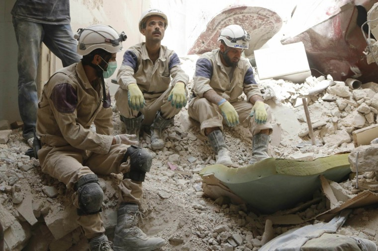Civil Defence members sit on rubble at a site hit by what activists said was a barrel bomb dropped by forces loyal to Syria's President Bashar al-Assad in Aleppo's Bustan al-Qasr neighborhood. (Hosam Katan/Reuters)