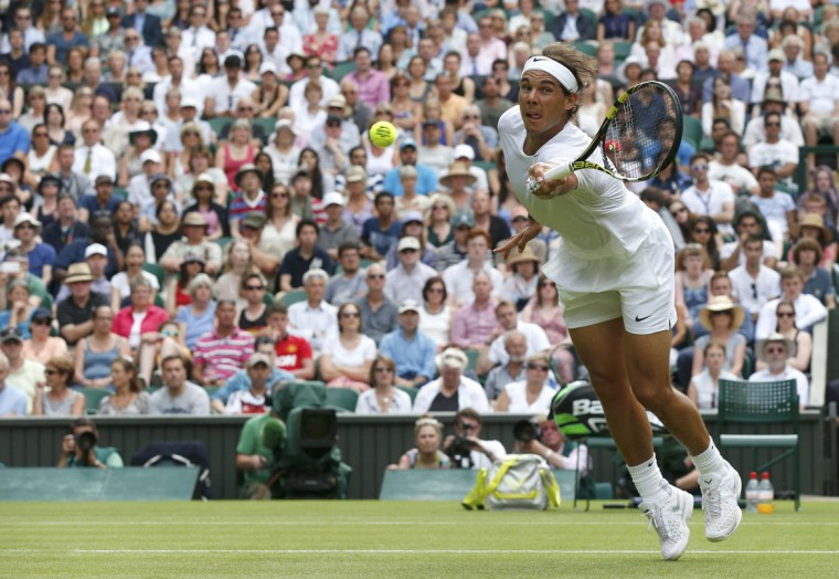 Rafael Nadal of Spain stretches to hit a return to Martin Klizan of Slovakia during their men's singles tennis match at the Wimbledon Tennis Championships, in London June 24, 2014. (REUTERS/Suzanne Plunkett)