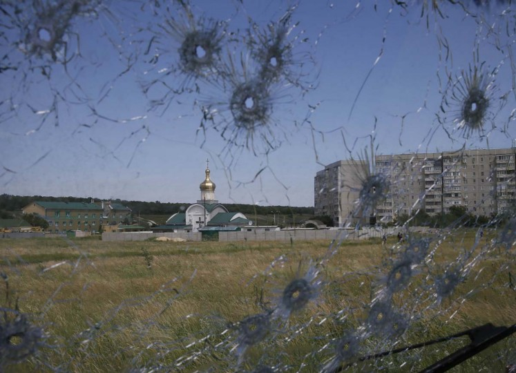 An Ukrainian border post is seen through bullet holes in a truck's windscreen on the outskirts of the eastern Ukrainian city of Luhansk June 3. Fighting raged in eastern Ukraine for the second straight day on Tuesday as the army rolled out an offensive against pro-Russia separatists holding the city of Slaviansk and claimed to have inflicted losses on the rebels.  || PHOTO CREDIT: GLEB GARANICH  - REUTERS