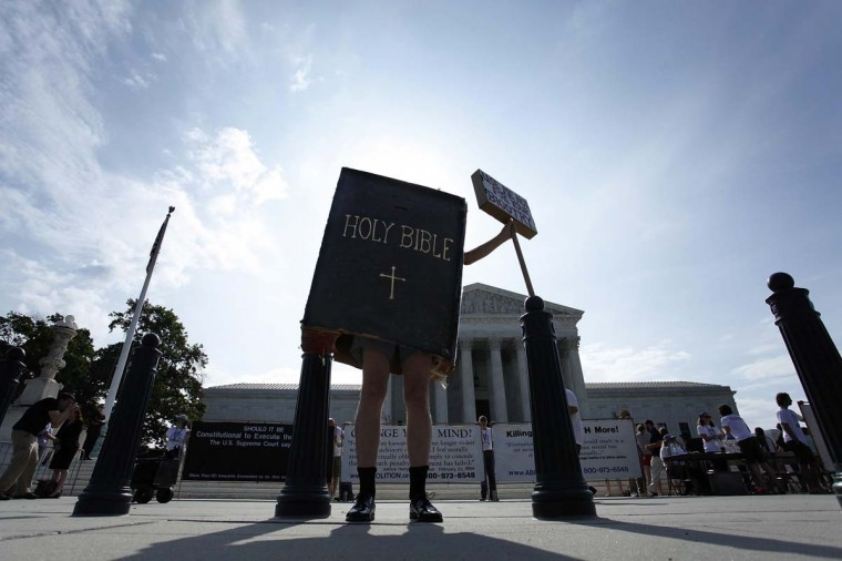 A protester dressed as a copy of the Bible joins groups demonstrating outside the U.S. Supreme Court in Washington June 30, 2014. The U.S. Supreme Court on Monday ruled that business owners can object on religious grounds to a provision of U.S. President Barack Obama's healthcare law that requires closely held companies to provide health insurance that covers birth control. (Jonathan Ernst/Reuters)