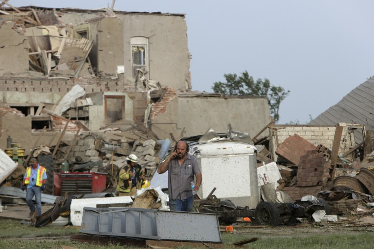 A man talks on the phone in front of tornado-damaged buildings in Pilger, Nebraska June 16, 2014. A swarm of tornadoes, some appearing two at a time, struck several farming communities in northeastern Nebraska on Monday, killing at least one person and injuring 16 in the tiny town of Pilger obliterated by a direct hit, officials said. (REUTERS/Lane Hickenbottom)