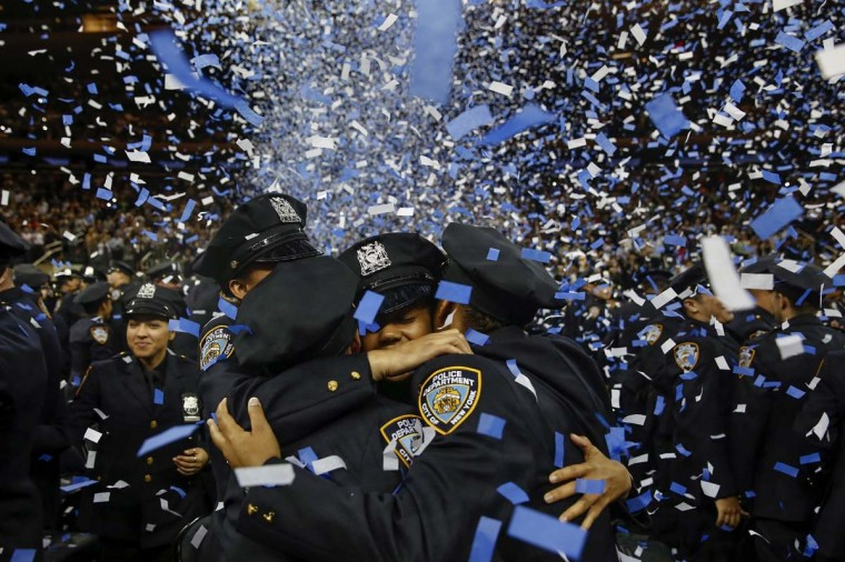 Members of the June 2014 graduating class of the New York City Police Academy embrace during their graduation ceremony at Madison Square Garden in New York June 30, 2014. (Shannon Stapleton/Reuters)