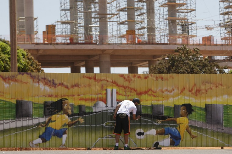 A man sprays soccer-inspired graffiti in the area around the National Stadium, as part of events prepared by the Federal District government to celebrate the countdown of 1,000 thousand days before the start of World Cup Brazil 2014, in Brasilia September 16, 2011. (REUTERS/Ueslei Marcelino)