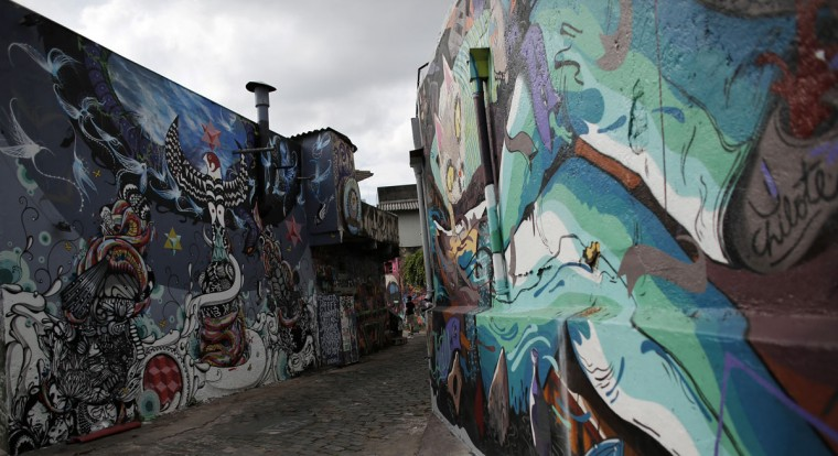 "A tourist walks between graffiti-filled walls along ""Beco do Batman"" (Batman's alley) in the Vila Madalena neighborhood, which is a well-known open-air graffiti museum, in Sao Paulo. (REUTERS/Nacho Doce)"