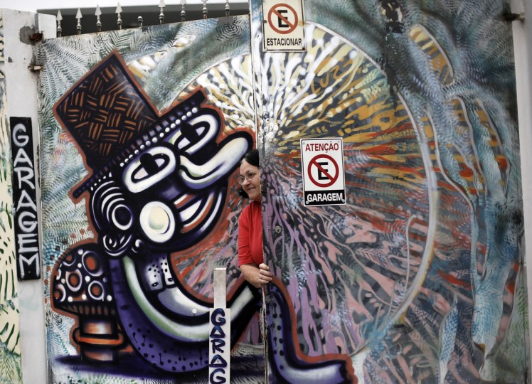 "A woman closes the door garage of her house between graffiti-filled walls along ""Beco do Batman"" (Batman's alley) in the Vila Madalena neighborhood, which is a well-known open-air graffiti museum, in Sao Paulo. (REUTERS/Nacho Doce)"