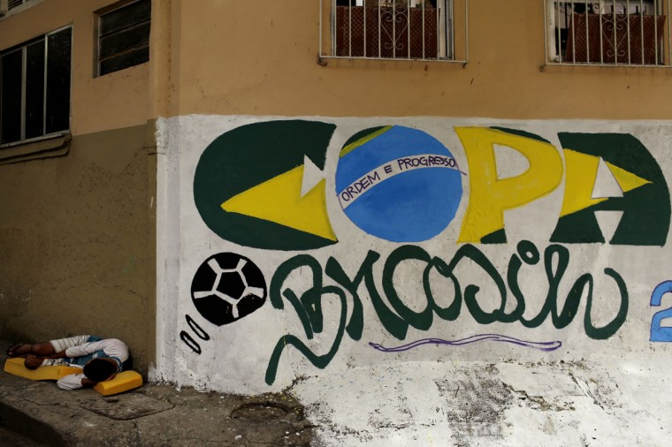 A man sleeps next to a graffiti referring to the upcoming World Cup in Rio de Janeiro. (REUTERS/Pilar Olivares)