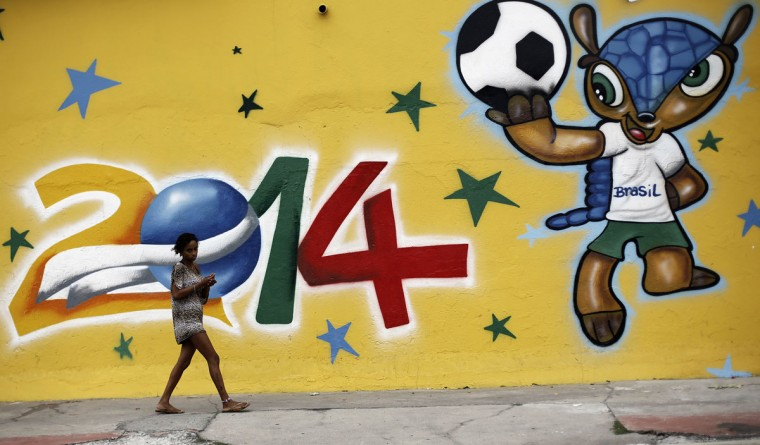 A woman walks past a graffiti painted with the official mascot of the 2014 World Cup, Fuleco the Armadillo, in Sao Paulo. (REUTERS/Nacho Doce)