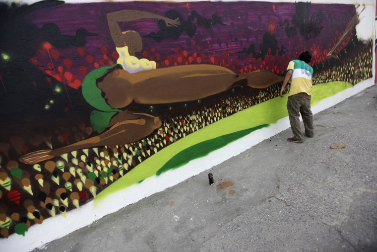 Graffiti artist Tarm works on a mural in celebration of the 2014 soccer World Cup in Rio de Janeiro. (REUTERS/Ricardo Moraes)
