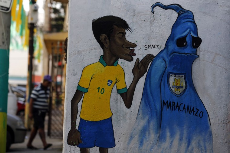 A man walks behind a graffiti depicting Brazilian soccer player Neymar and a phantom representing the Uruguayan soccer team, who won the 1950 World Cup in Brazil, in Rio de Janeiro. (REUTERS/Sergio Moraes)