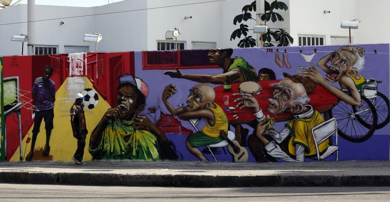 A man walks past by graffiti painted on the a wall in reference to the 2014 World Cup in Rio de Janeiro. (REUTERS/Sergio Moraes)