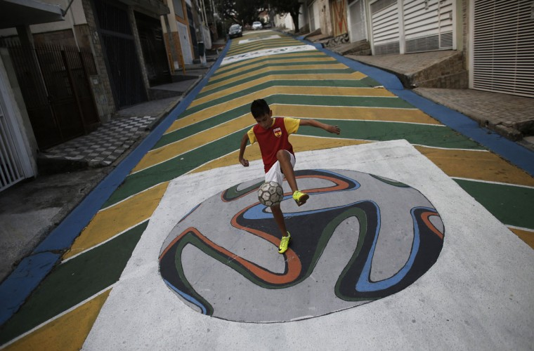 "Gabriel, 14, plays soccer on graffiti painted with the official match ball for the 2014 World Cup named ""Brazuca"" on a street in Sao Paulo. (REUTERS/Nacho Doce)"