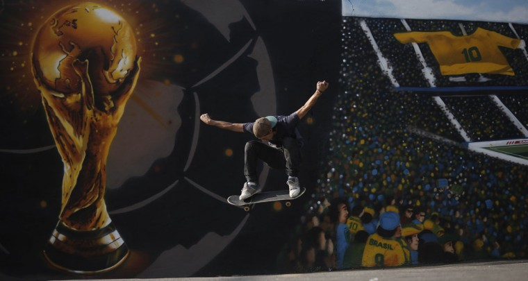 Juliano Ferrari performs with his skateboard next to a graffiti of the World Cup trophy and Brazil soccer fans, referring to the upcoming 2014 World Cup soccer tournament, in Sao Paulo. (REUTERS/Nacho Doce)