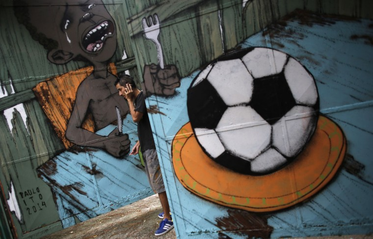 Brazilian artist Paulo Ito talks on his mobile phone next to graffiti he painted referencing the 2014 World Cup, on the door of a public schoolhouse in Sao Paulo. (REUTERS/Nacho Doce)