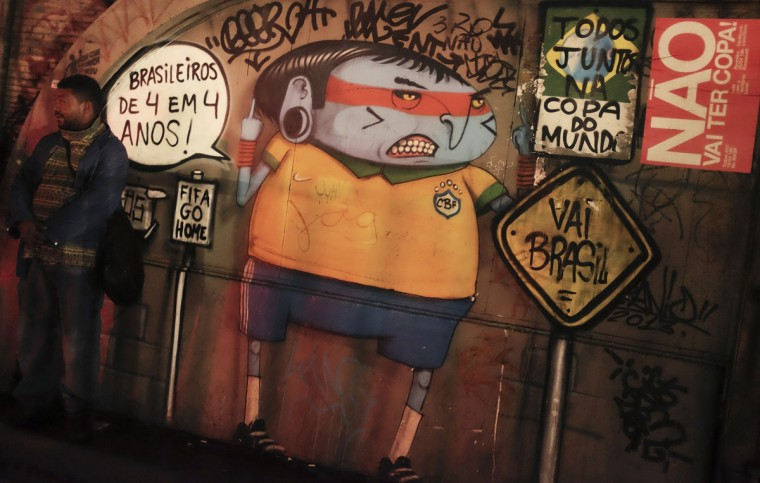 A man stands next to graffiti referring to the 2014 World Cup in Sao Paulo. (REUTERS/Nacho Doce)