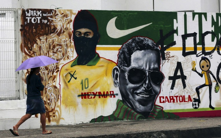 A woman walks past a graffiti referencing the 2014 World Cup and with Brazilian soccer player Neymar's face covered with a mask, in Rio de Janeiro. (REUTERS/Ana Carolina Fernandez)