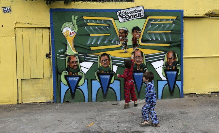 Kids play near graffiti referencing the 2014 World Cup on Taturana street at Vicente de Carvalho neighborhood in Rio de Janeiro. (REUTERS/Sergio Moraes)