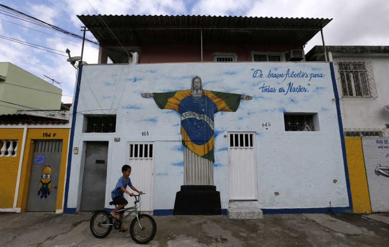 A boy rides his bicycle past graffiti depicting the iconic statue of Christ the Redeemer with a Brazilian flag design, referencing the 2014 World Cup, on Taturana street at Vicente de Carvalho neighborhood in Rio de Janeiro. (REUTERS/Sergio Moraes)
