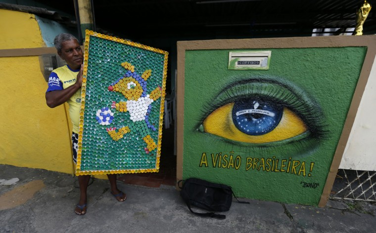 A man holds up a board made with recycled bottles next to graffiti referencing the 2014 World Cup on Taturana street at Vicente de Carvalho neighborhood in Rio de Janeiro. (REUTERS/Sergio Moraes)
