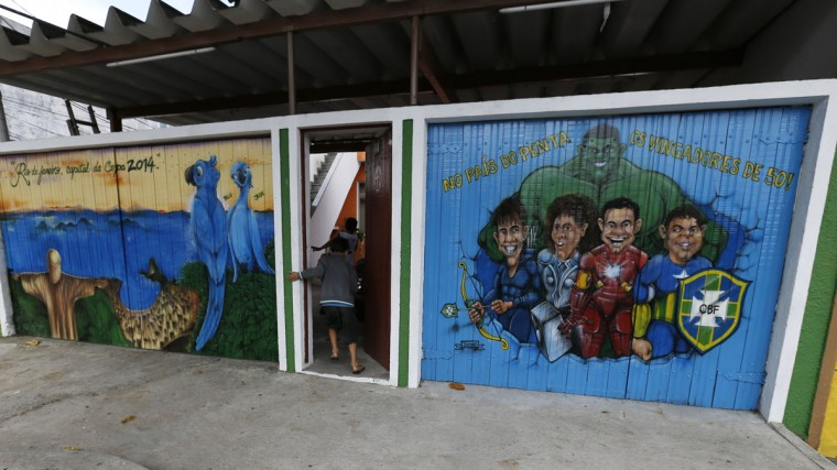 Children run into their house decorated with graffiti referencing the 2014 World Cup on Taturana street at Vicente de Carvalho neighborhood in Rio de Janeiro. (REUTERS/Sergio Moraes)
