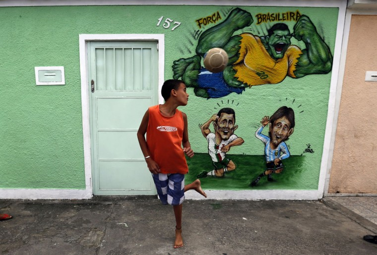 A boy controls a ball next to graffiti depicting soccer players Brazil's Hulk (top), Portugal's Cristiano Ronaldo and Argentina's Lionel Messi (bottom right), referencing the 2014 World Cup on Taturana street at Vicente de Carvalho neighborhood in Rio de Janeiro. (REUTERS/Sergio Moraes)