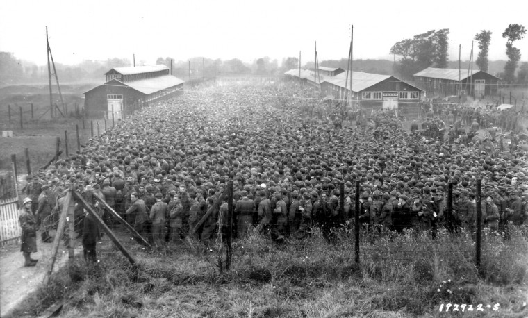 German prisoners of war captured after the D-Day landings in Normandy are guarded by U.S. troops at a camp in Nonant-le-Pin, France, on Aug. 21, 1944 in this handout photo provided by the US National Archives. (US Army photo)