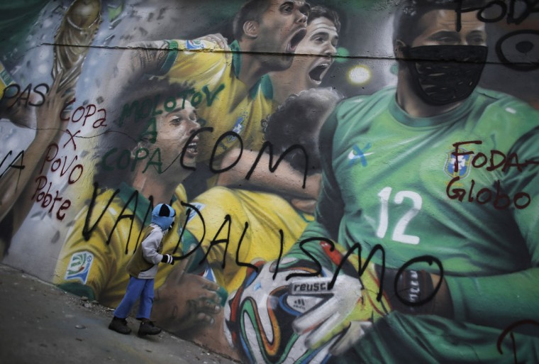 A child walks in front of a graffiti by Brazilian artist Rodolfo Turini in reference to the 2014 World Cup, with Brazilian soccer players goalkeeper Julio Cesar's face covered by a mask, in Sao Paulo. (REUTERS/Nacho Doce)