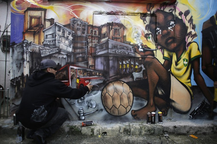 Brazilian artist Bone, a member of OPNI, puts the final touches to his graffiti on a wall, in reference to the 2014 World Cup, in the Vila Flavia slum of Sao Paulo. (REUTERS/Nacho Doce)