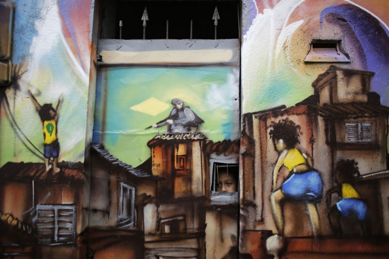 A child looks out from the window of his home painted with graffiti by members of OPNI, in reference to the 2014 World Cup, in the Vila Flavia slum of Sao Paulo. (REUTERS/Nacho Doce)