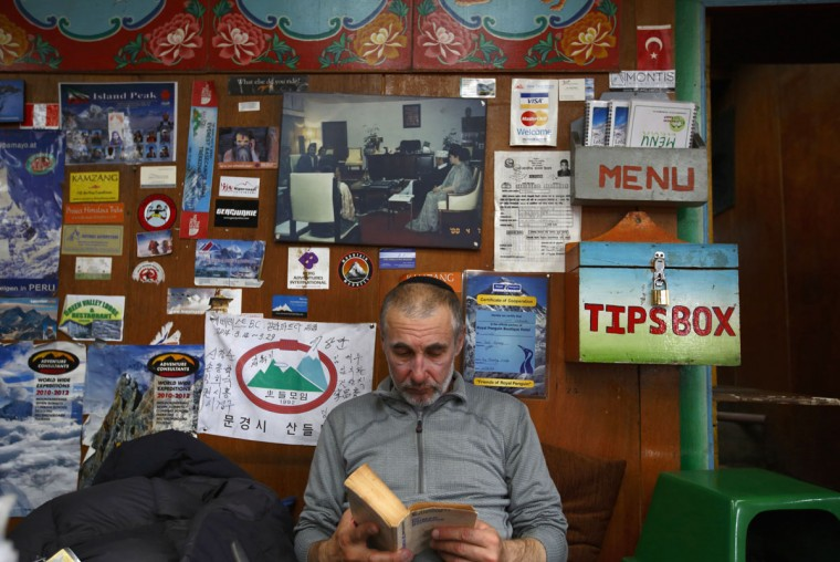 American climber Alex Goldfarb, who had to cancel his planned climb of Mount Lhotse, reads a book in the Solukhumbu District. (REUTERS/Navesh Chitrakar)