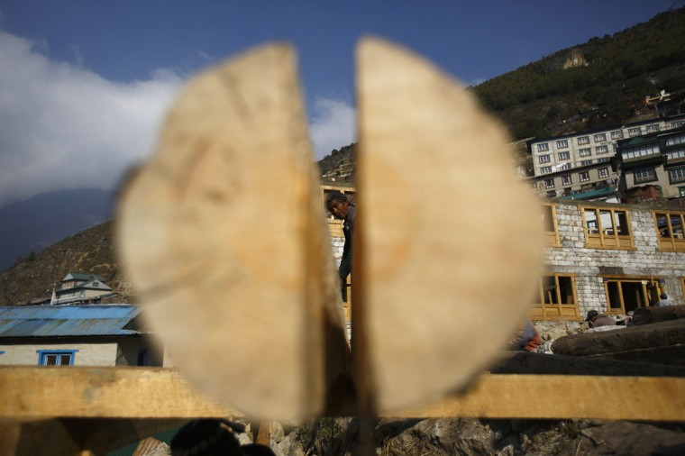 A construction worker is seen through a split tree trunk while building a hotel in Namche, approximately 3,400 meters above sea level in the Solukhumbu District. (REUTERS/Navesh Chitrakar)