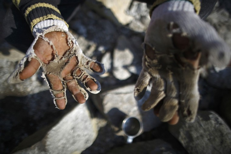 A construction worker shows his torn gloves as he carves stones while building a hotel in Namche, approximately 3,400 meters above sea level in the Solukhumbu District. (REUTERS/Navesh Chitrakar)