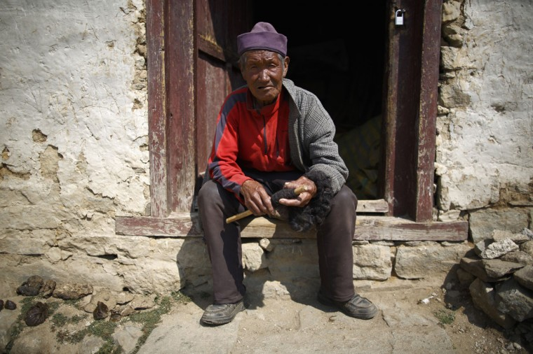 Khunjung Sherpa, 90, who earned $0.09 a day when he worked as a porter, sits outside his house in Namche, Solukhumbu District April 27, 2014. (REUTERS/Navesh Chitrakar)