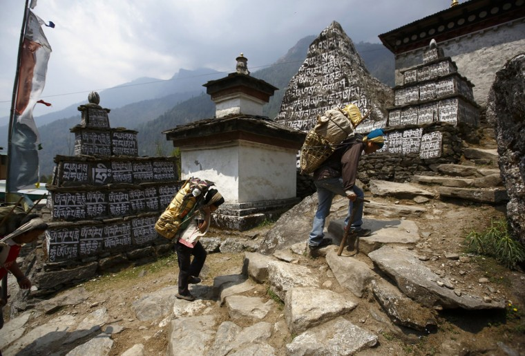 Kedar Rai (right), 42, and his sons carry goods to their shop in the Solukhumbu District on April 26, 2014. (REUTERS/Navesh Chitrakar)