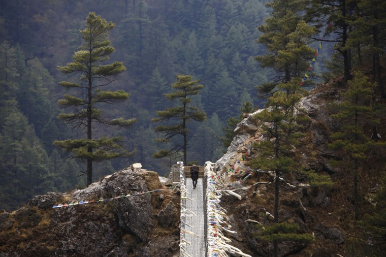 A porter crosses a bridge while on his way back from Namche, approximately 3.400 meters above sea level in Solukhumbu District April 26, 2014. (REUTERS/Navesh Chitrakar)