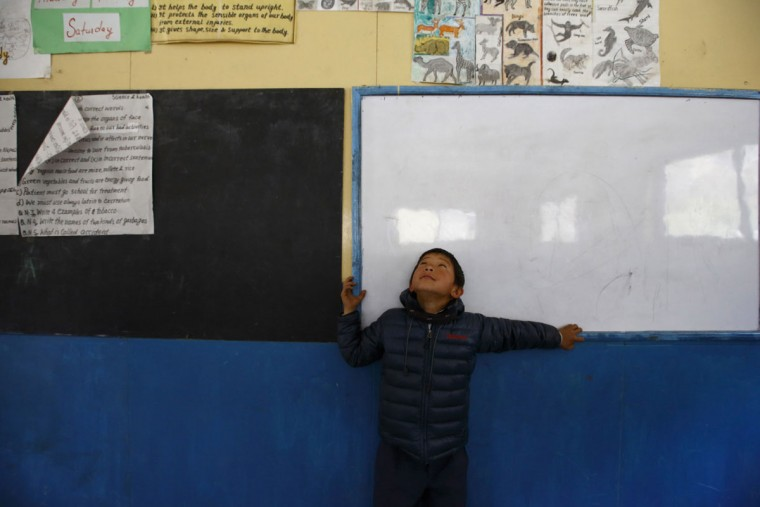 A boy plays near a white board inside a classroom at Khumjung High School, which was founded in 1961 by Sir Edmund Hillary, the first climber to reach the summit of Mount Everest, in Khumjung, approximately 3,700 meters above sea level in the Solukhumbu District on April 30, 2014. (REUTERS/Navesh Chitrakar)