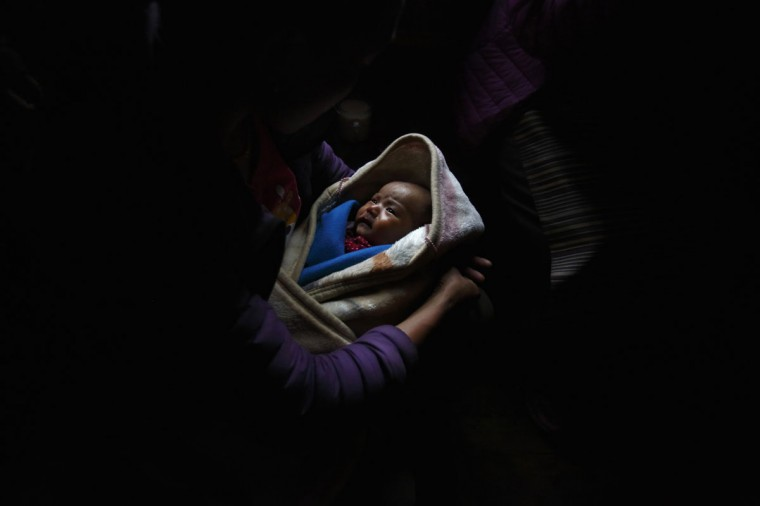 50-day-old Pasang Choti Sherpa, whose father, Lakpa Sherpa, died in the avalanche on April 18 2014, lies on her mother's lap in Khumjung, approximately 3,700 meters above sea level in the Solukhumbu District on May 8, 2014. (REUTERS/Navesh Chitrakar)